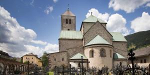 """Der """"Dom zu Innichen"""" ist Tirols bedeutenster romanischer Sakralbau. Er erinnert an den Festungsstil der Kreuzritter zur Zeit der Stauferkaiser. Mit dem Bau der Stiftskirche (dem """"Dom zu Innichen"""") wurde im Jahr 1143 begonnen; ein Brand im Jahr 1200 zwang zu einem Neuanfang. 1280 war der heutige Baukörper abgeschlossen. In den Jahren 1323 bis 1326 wurde der Glockenturm neu hinzu gebaut. Der """"Dom zu Innichen"""" ist der bedeutenste Sakralbau im romanischen Stil in den Ostalpen mit beeindruckenden kunsthistorischen Schätzen sowie einer kleine Bibliothek mit seltenen und zum Teil einzigartigen Handschriften."""